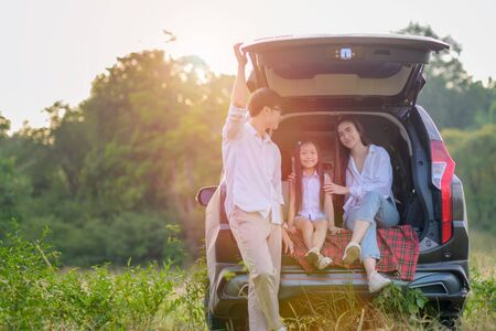 happy family enjoy relax in back seat of the car, closely to the meadow  field nature together