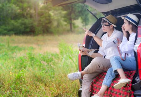 couple lover sitting back cap of the car, enjoy the forest nature together on traveling