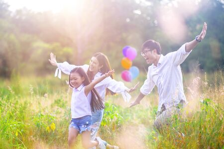 group of warm family enjoy playing together in wildflowers meadow field at light of morning sunrise 写真素材