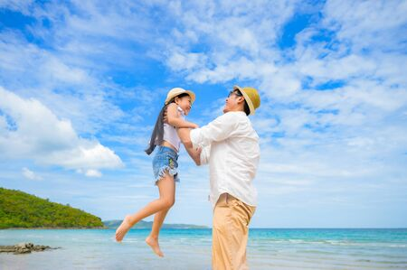 father holding drauther to flying around on the sea beach, playing fun together on Vacation and holidays between father and drauther, Dad takes care alone kid