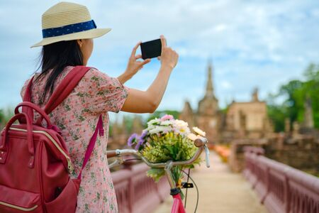 woman tourist enjoy riding local bicycle to see the historic park of Thailand, exciting taking photo to the wonderful place of sightseeing