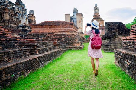 woman tourist enjoy walking to see the historic park of Thailand, exciting taking photo to the wonderful place of sightseeing 版權商用圖片