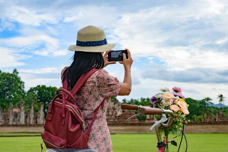 woman tourist enjoy riding local bicycle to see the historic park of Thailand, exciting to explore the wonderful place of sightseeing