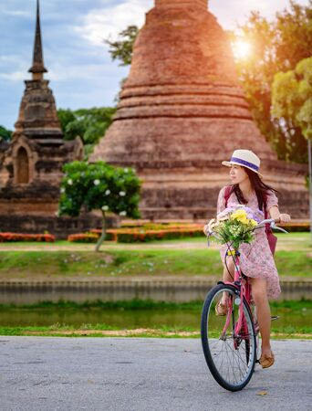woman tourist enjoy riding vintage bicycle to see the historic park of Thailand, exciting to explore the wonderful place of sightseeing