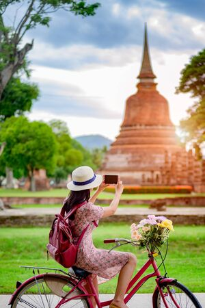 woman tourist enjoy riding vintage bicycle to see the historic park of Thailand, exciting taking photo to the wonderful place of sightseeing