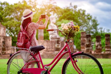 woman tourist enjoy riding vintage bicycle to see the historic park of Thailand, exciting taking photo to the wonderful place of sightseeing 版權商用圖片