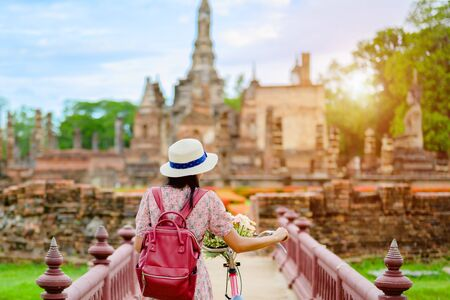 woman tourist enjoy walking to see the historic park of Thailand, exciting to explore the wonderful place of sightseeing