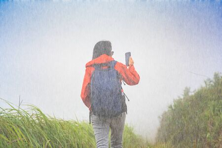 woman walking in rain shower looking the direction route with mobile device, lose of signal of mobile at far from city, lost the way or find destination on the hill