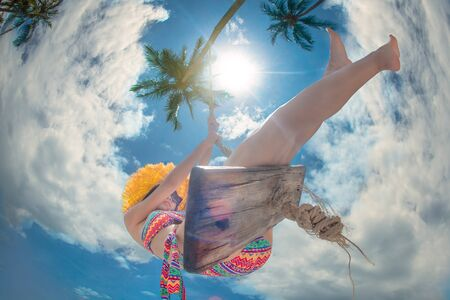 low angle view of young woman playing around on wooden swing under palm tree at sunny on the island, summer time vacation and weekend relax funny happy time