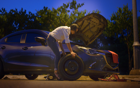 Woman try to fix problem of car by herself with belonging tools, need help and assistant at dark of the night, scary and worry alone in the dark, car engine failure or tire need replacement 報道画像