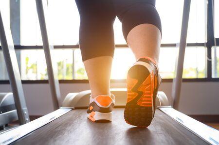 closeup of leg of fat woman being run or jog on belt of treadmill machine Stockfoto