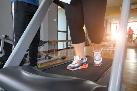 leg of fat woman being run or jog on belt of treadmill machine, workout under intruction of trainer