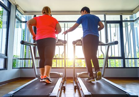man trainer coach and fat woman being run or jog on belt of treadmill machine, workout under instruction of personal coach