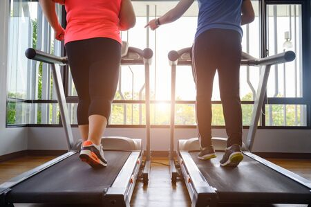 leg of man trainer coach and fat woman being run or jog on belt of treadmill machine, workout under instruction of personal coach