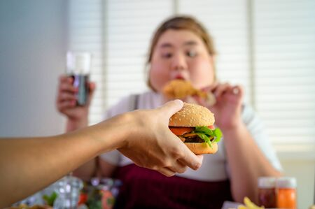hamburger being serv to woman hunger in background, junk food eating a lot by fatty woman