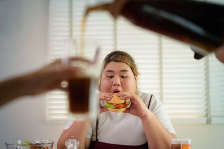 plump fatty woman hunger eating a lot junk food with high calories beverage drink in forground Stockfoto