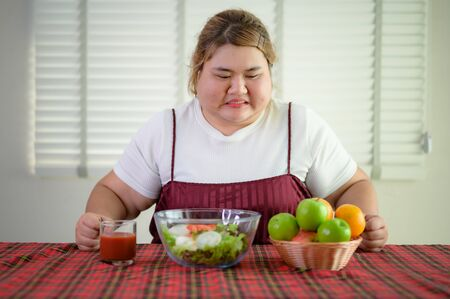 plump fatty woman anti and refused to eat salad vegetable and fruit on table, do not wants to eat salad food, against vegetable green salad, un-preferable fruit vegetable salad Banco de Imagens