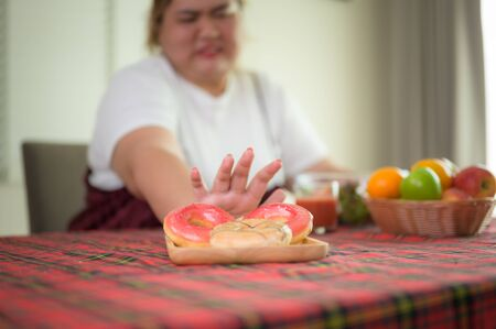 sweet desert donut on table refused or anti to eat by plump fatty woman, do not wants to eat sweet or junk food, against sweet high calories , un-preferable weight and fatty