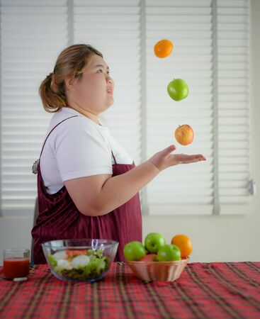 plump fatty woman loves and enjoy playing salad fruits meal