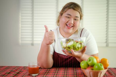 plump fatty woman enjoy and happy loves to eat salad vegetable and fruit on table Stockfoto