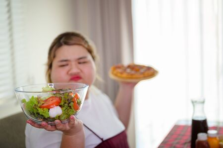 Vegetable in bowl on hand of plump fatty woman, in motion anti and refused to eat, do not wants to eat salad food, against vegetable green salad, preferable to eat pizza Stock Photo