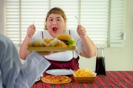 plump fatty woman hunger enjoy eating a lot junk food with another high calories hamburger bread serving in foreground Banco de Imagens
