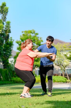 coach or trainer in action support fat plump woman in exercise to reduce body weight Stock Photo