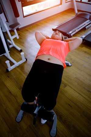 Plump fat woman in motion of working out exercise in gymnasium