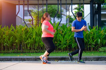 plump fat woman and coach or trainer running together in village park, support and suggestion to diet reduce of weight Stock Photo