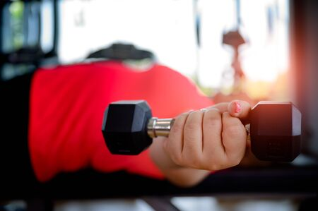 hand of fat plump woman holding weight Dumbbell in gymnasium, workout reduce body weight Stock Photo