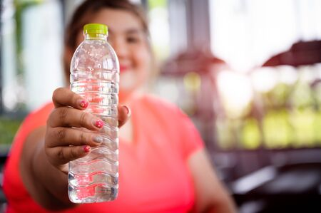 water bottom in hand of fat plump waman ready to serving at  thirsty during exercise