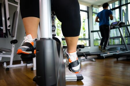 legs of fat plump woman step on riding maching for exercise