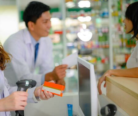hand of woman pharmacist holding box or case of medicine container, estimation cost of the pills in charge, with customer and consultant 写真素材