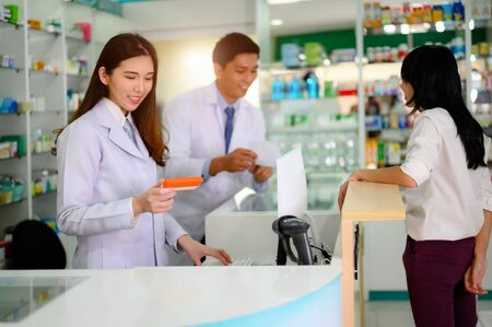 hand of woman pharmacist holding box or case of medicine container, estimation cost of the pills in charge, with customer and consultant Stok Fotoğraf - 132932118