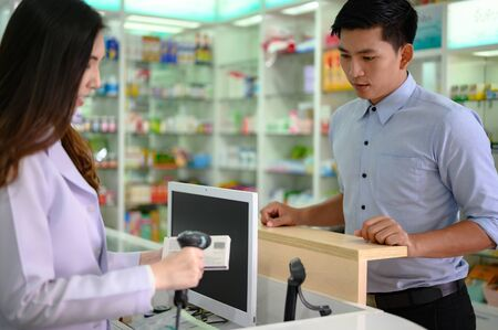 asian man customer of pharmacy store worry in ill or sick, buying medicine hiself at sick time period