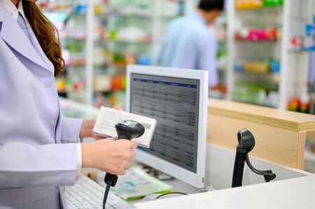 hand of woman pharmacist holding scanner bar code on box or container of medicine, checking to sell to customers in pharmacy drug store