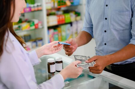 hands of selling pharmacist and man customers buyin medicine in drug store Reklamní fotografie