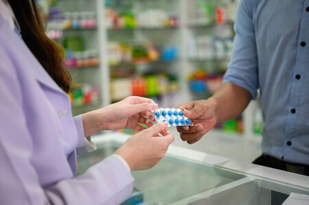 hands of selling pharmacist and man customers buyin medicine in drug store, handover pills of medicine from hand to another hand charge