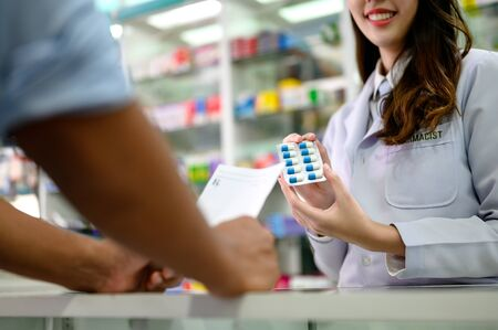 medicine bundle in hands of selling pharmacist offer to man customers buying in drug store, prescription order pills instruct by doctor specialist Reklamní fotografie