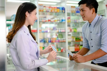 asian man customer or buyer of phamacy drug store in discussion of the medicine property effect, buying pill under prescription order