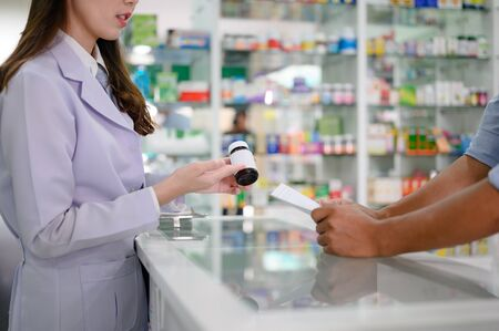 bottle of medicine tablets or pills in hand of woman pharmacist in explanation apply to man customer, discussion in property of medicine how to apply to the outpatient