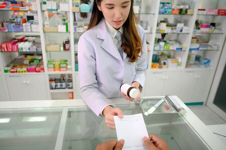 woman pharmacist in takes order of prescription from customer