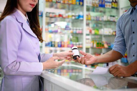 medicine pill bottle handover from waman pharmacist to hand of man customer in pharmacy drug store