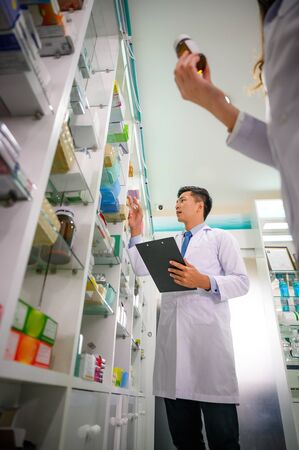 man doctor and woman pharmacist in charge of checking inventory list of medicine remaining or balance in stock, working together in pharmacy drug store
