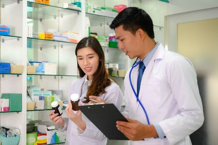 woman pharmacist and doctor checking inventory list of medicine remaining or balance in stock, working together in pharmacy drug store