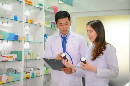 doctor and woman pharmacist in charge of checking inventory list of medicine remaining or balance in stock, working together in pharmacy drug store