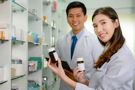 woman pharmacist and doctor in charge of checking inventory list of medicine remaining or balance in stock, working together in pharmacy drug store