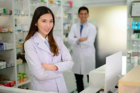 woman and man pharmacist are stand by in charge in pharmacy drug store