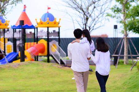 warm family takes kid child to the park playground Banco de Imagens