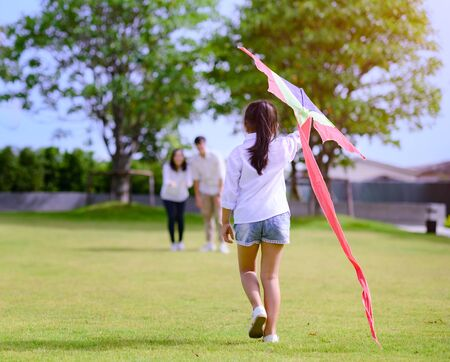 a little girl daughter run o family with holding kite in hand t in field park of village Banco de Imagens